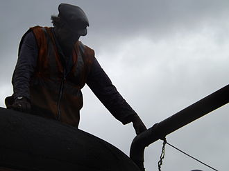 Fireman (steam engine) - A fireman refills the water tank of 34067 'Tangmere'.