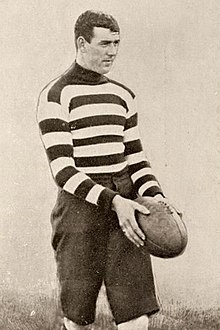 A dark-haired footballer in a long-sleeve horizontally-striped guernsey holding a football
