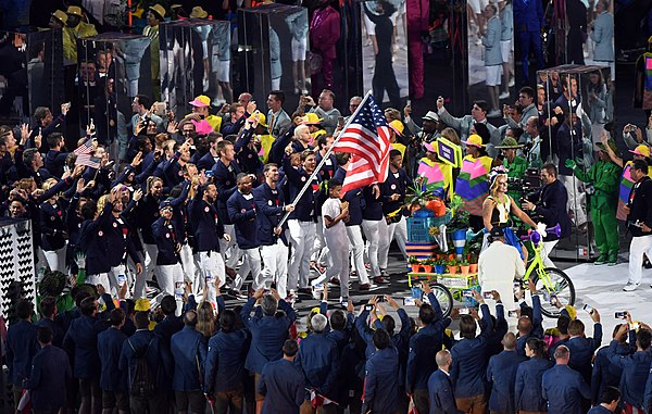 Phelps carrying the flag on behalf of athletes from the United States during the parade of nation within the 2016 Summer Olympics opening ceremony Phelps carries Stars & Stripes (28726351981).jpg