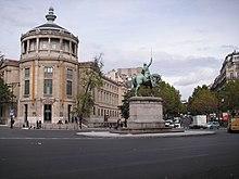 Fargefotografi av et firkant prydet med en statue av en rytter, til venstre en rotundebygning, til høyre en allé