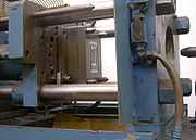 Paper clip mold opened in molding machine; the nozzle is visible at right