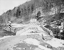 "Black and white photograph looking along the roadway of a bridge flanked by low stone walls with a large ""ROAD CLOSED"" sign on the bridge. Snow covers some of the bridge and the forested hillside in the background."