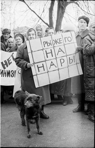 """Privatization in Russia - Russians protest the economic depression caused by the reforms with the banner saying: """"The redhead should be in jail!"""", 1998."""