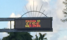 A variable-message sign over a road that reads 'Pokémon Go is a no-go when driving'.