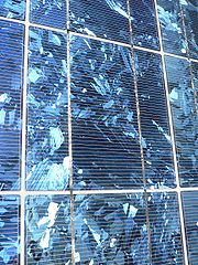 Polycrystaline PV cells laminated to backing material in a PV module