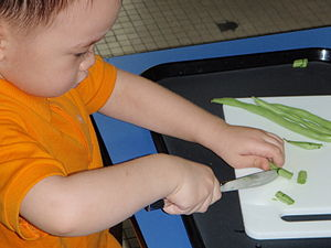 English: A child slicing yardlong beans at The...
