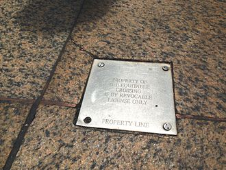 A metal plaque on the sidewalk of New York City to declare that the crossing onto the private property is a revocable license to protect it from becoming an easement by prescription. Property line, crossing is by revocable license only.jpg