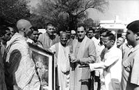 A black-and-whitу photo of Rajiv Gandhi holding a book and surrounded by Russian Hare Krishnas