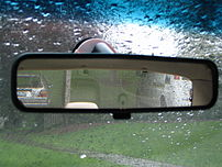 The rear-view mirror of a Mazda 626. It shows ...