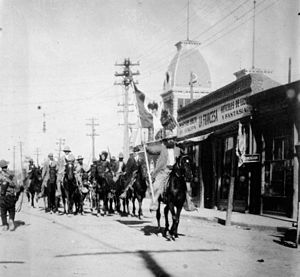 Black-and-white photograph of a group of men on horseback on a city street. Lead horsemen is carrying a flag.