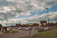 Several rows of cars parked in an outdoor parking lot under a blue sky with billowy clouds.  Many buildings are in the background.