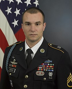 Head and torso portrait of Staff Sergeant Giunta in the Army Service Uniform with a U.S. flag in the background
