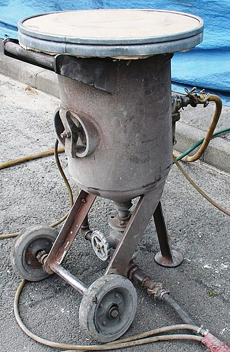 Abrasive blasting - Device used for adding sand to the compressed air (top of which is a sieve for adding the sand)