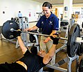 Senior Airman Danielle Galich spots Senior Airman Carnell Robinson as he lifts weights.jpg