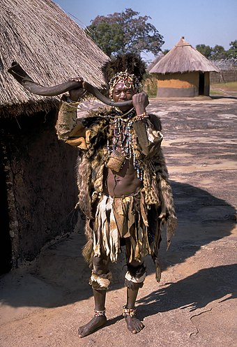 A n'anga (Traditional Healer) of the majority (70%) Shona people, holding a kudu horn trumpet Shona witch doctor (Zimbabwe).jpg