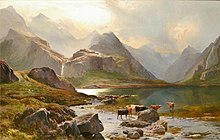 Tall, rocky mountains tower over a small lake, beyond which a waterfall cascades down from the heights. Brown and black cattle stand by the lakes margins, lit by wan sunlight that streams through the clouds.