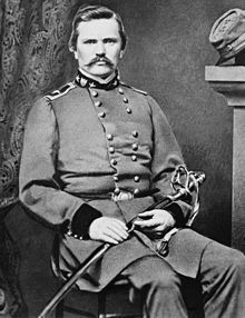 Black-and-white photo of a mustachioed military officer sitting with a saber across his lap