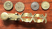 A handheld metal balance for weighing sovereigns and half sovereigns, along with several pieces that approximate the diameter or weight of those two coins