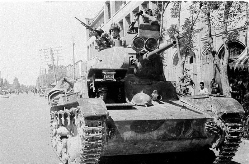 Soviet tankmen of the 6th Armoured Division drive through the streets of Tebriz