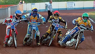 Motorcycle speedway - All 4 riders leaning into the first corner - note the elbows.