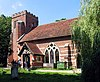 A red brick church with white stone banding and a red tiled roof seen from the southeast, showing the body of the church with a large window, a porch, and a battlemented tower
