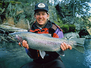 English: Man holding a rainbow trout (Oncorhyn...