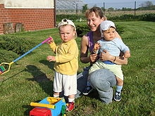 A young mother kneels in a garden with her two children. A baby sits astride her knee facing outwards and looking away from the camera. A toddler stands slightly in front of his mother holding a spade and frowning at the camera.