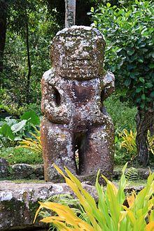 Photo d'une statue de tiki en pierre de deux mètres cinquante de haut. Le bras gauche est manquant.