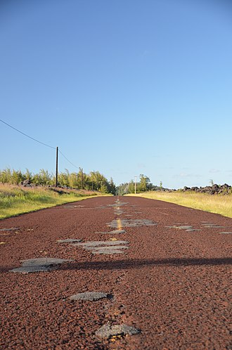 Hawaii Route 137 - A section of the Red Road with pavement containing Hawaiian volcanic red cinder, never having been repaved with black asphalt (2012)