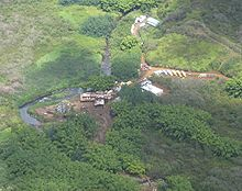 An overhead view of a set of buildings located in a dense jungle. A river runs to the left of the buildings, and moving trucks are seen to the right of the buildings. There is a dirt road leading from the buildings to other buildings.