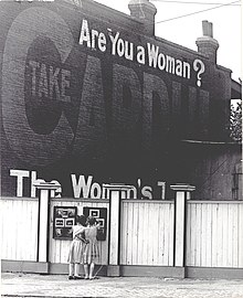 "Two girls examining a bulletin board posted on a fence. An advertisement painted above them asks ""Are You a Woman?""."