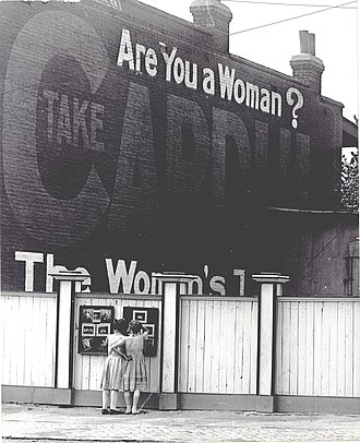 "Two girls examining a bulletin board posted on a fence. An advertisement painted above them asks ""Are You a Woman%3F"".jpg"