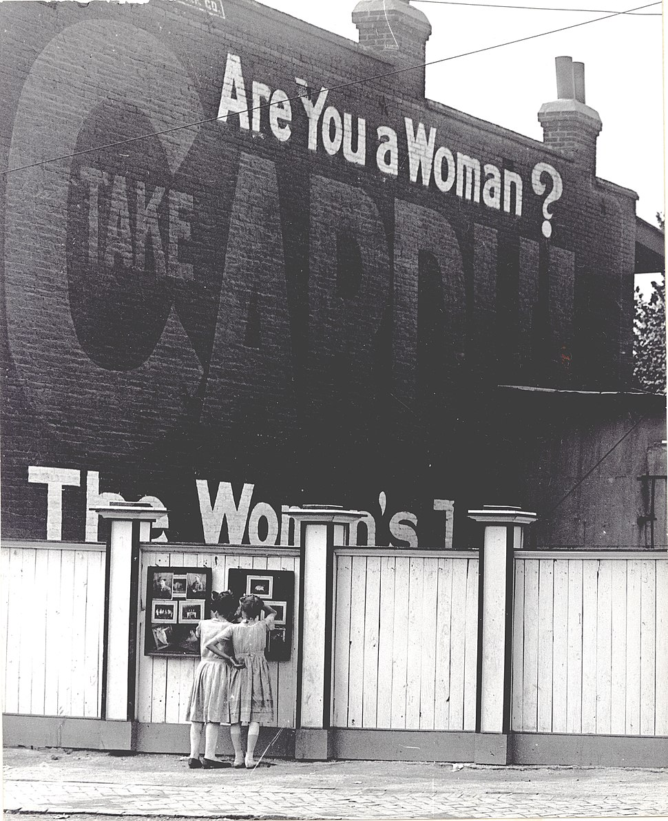"Two girls examining a bulletin board posted on a fence. An advertisement painted above them asks ""Are You a Woman?"""