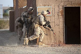 Yuma Proving Ground - Marines prepare to breach a building during a mock helicopter raid at YPG, part of the U.S. Marine Corps' Weapons and Tactics Instructor Course