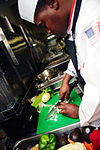"U.S. Navy Culinary Specialist 1st Class Damion Thompson chops vegetables during the first ever ""Iron Chef"" competition May 17, 2013, aboard the aircraft carrier USS George H.W. Bush (CVN 77) 130517-N-XE109-049.jpg"