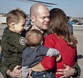 U.S. Navy Lt. Cmdr. P.J. Williamson, center, assigned to Helicopter Maritime Strike Squadron (HSM) 75, embraces his wife, Meredith, and children during the squadron's homecoming at Naval Air Station North 131211-N-DZ075-071.jpg