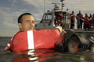 A Coast Guardsman demonstrating the heat escap...