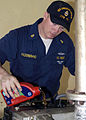 US Navy 050117-N-6736W-220 Chief Engineman Jeff Hilderbrand of Sporan, Wash., assigned to USS Abraham Lincoln (CVN 72), pours oil into a generator that will provide power to Indonesian Government offices.jpg