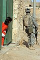 US Navy 060317-M-9019H-091 An Iraqi child watches Pfc. Joel H Timarong assigned to the 36 Infantry regiment, patrol through the city of Hit, Iraq, during Operation Iraqi Freedom.jpg