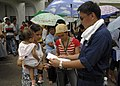 US Navy 070623-N-4954I-174 Aviation Boatswain's Mate (Handling) 3rd Class John Paul Onglatco, attached to amphibious assault ship USS Peleliu (LHA 5), reviews medical paperwork for a Filipino mother and her daughter in front of.jpg