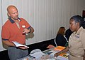 US Navy 070726-N-2510R-003 Chief Personnel Specialist Patricia Aughtry talks to William Yaeger, Empire State College outreach assistant, at the first Education Fair for Precommissioning Unit (PCU) George H.W. Bush (CVN 77).jpg