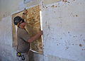 US Navy 070922-N-3560G-024 Builder 3rd Class Anthony Reeder, attached to Naval Mobile Construction Battalion (NMCB) 4, uses a sheet of plywood to seal an opening in a wall during the conversion of an old Iraqi prison.jpg