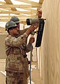 US Navy 080430-N-5709C-003 Builder Constructionman Philip Riley, a Seabee assigned to Naval Mobile Construction Battalion (NMCB) 3, instructs an Iraqi soldier on how to use a pneumatic nail gun.jpg