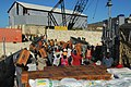 US Navy 080926-N-4515N-105 Haitian civilians unload relief supplies from a landing craft utility assigned to Assault Craft Unit (ACU) 2 embarked aboard the amphibious assault ship USS Kearsarge (LHD 3).jpg