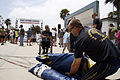 US Navy 090617-N-7603L-108 Jim Woods, a retired Navy SEAL assigned to the U.S. Navy Parachute Team, the Leap Frogs, speaks with spectator Carlos Moleda as he packs his parachute following a team parachute demonstration.jpg