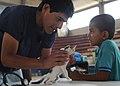 US Navy 110605-N-NY820-284 Dr. César Jayashi Flores examines a boy's cat at a temporary veterinary clinic.jpg