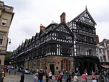 The corner of a street with a range of shops running up the right side of the street; the shops have stone lower storeys and highly detailed timber-framed upper storeys that include oriel windows and gables.  To the right of the range of shops is another shop with a modern shop front; it is taller than the others, and is timber-framed above the ground floor.