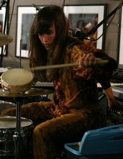 A 32-year-old woman with long brown hair, and a yellow and brown outfit. She is playing drums, and is surrounded by music equipment.