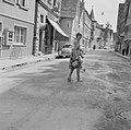 Vrouw besproeit een straat met een gieter, Bestanddeelnr 254-3943.jpg