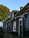 foto van Perceelsgedeelte van een houten huis met topgevel